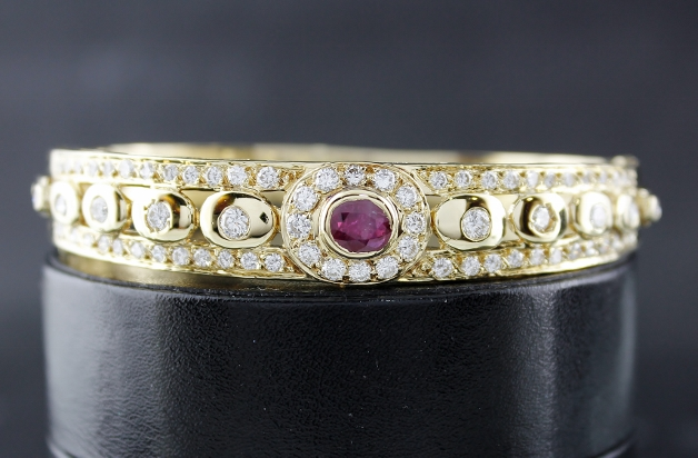 A 18K YELLOW GOLD DIAMOND AND RUBY BANGLE