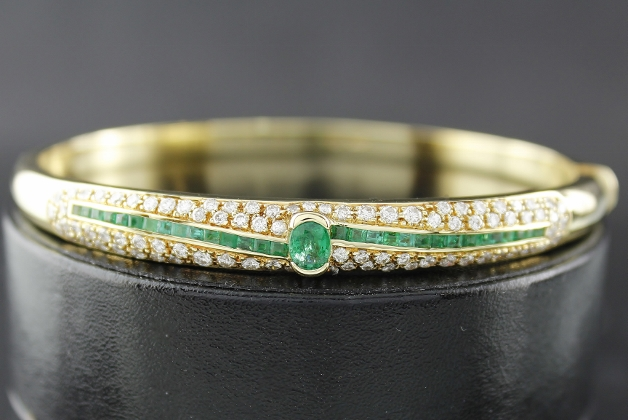 A 18K YELLOW GOLD DIAMOND AND EMERALD BANGLE